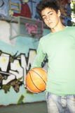 A teenage boy standing with a basketball. Royalty Free Stock Photography