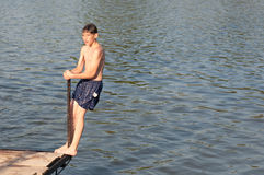 Teenage boy standing on the edge of wooden dock. On sunny summer day Royalty Free Stock Image