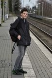 Boy waiting for the train. Teenage boy standing on platform at station waiting for the  train Royalty Free Stock Images