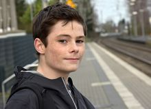 Boy waiting for the train. Teenage boy standing on platform at station waiting for the  train Stock Image
