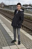 Boy waiting for the train. Teenage boy standing on platform at station waiting for the  train Royalty Free Stock Photo