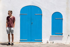 Teenage boy standing relaxed. Teenage boy with sunglasses standing relaxed and looking. Mediterranean style white building with closed blue colored doors and Royalty Free Stock Photo