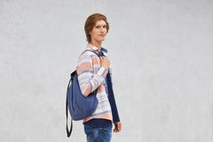 Teenage boy standing sideways holding rucksack wearing shirt and jeans posing against white concrete wall with copy space for your Royalty Free Stock Images