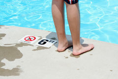 Teenage boy standing by a swimming pool Stock Photos