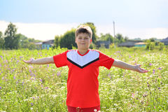 Teenage boy stands in meadow arms outstretched to the sides Royalty Free Stock Image