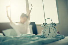 Teenage boy stretching hands after wakeup in bed stock photo