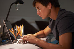 Teenage Boy Studying At Desk In Bedroom In Evening On Laptop Stock Images