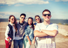 Teenage boy with sunglasses and friends outside Stock Images