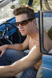 Teenage boy (17-19) in sunglasses sitting in driver's seat of convertible car, close-up, side view Stock Photos