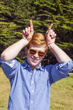 Teenage boy with sunglasses walks on the meadow Stock Photo