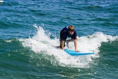 Teenage Boy Surfing. A teenager surfing. The boy is just beginning to stand up on the surfboard Stock Image