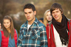 Teenage Boy Surrounded By Friends. In Outdoor Autumn Landscape Royalty Free Stock Images