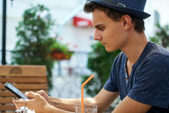 Teenager texting from his mobile phone. Teenage boy at a table in the restaurant, texting from his mobile phone Royalty Free Stock Photos