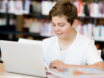Teenage boy with tablet in library Royalty Free Stock Images