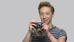 Teenage boy takes a photo with vintage camera. Cute teen guy using retro photo camera against gray background. Youth, technology and hobby concept stock footage