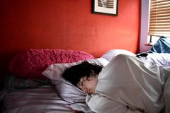 Teenage Boy Taking a Nap in Bedroom Stock Image