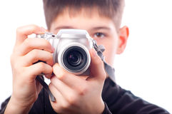 Teenage boy taking photos with small camera. Isolated on white Royalty Free Stock Image