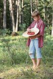 Teenage boy tasting fresh forest wildberries Stock Images