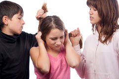 Teenage boy and teenage girl pulling hair of smaller teenage girl Stock Photography