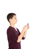 Teenage boy texting on his mobile. Handsome young teenage boy standing sideways texting on his mobile phone isolated on white Stock Photo