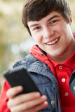 Teenage Boy Texting On Smartphone. Wearing Winter Clothes Stock Photo