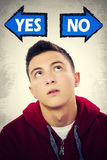 Teenage boy thinking what to choose between YES and NO Royalty Free Stock Images