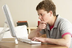 Teenage Boy in Thought Studying at Home Stock Photo