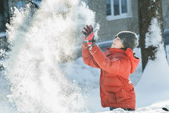 Teenage boy tossing up natural snow in frosty winter sunny day outdoors Royalty Free Stock Photography