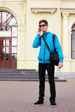 Teenage Boy Traveler. Smiling teenage traveler standing at the station and using cellphone Stock Images