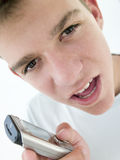 Teenage boy using cellular phone and looking mad Royalty Free Stock Image