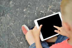 Teenage boy using a digital tablet in the street Stock Photo