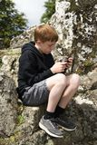 Teenage boy using his smart phone outside royalty free stock photo