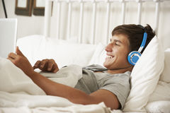 Teenage Boy Using Laptop And Headphones In Bed At Home Stock Images