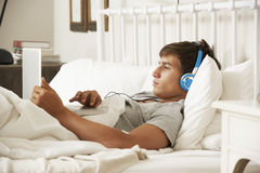 Teenage Boy Using Laptop And Headphones In Bed At Home Royalty Free Stock Photos