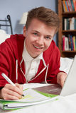 Teenage Boy Using Laptop For Homework In Bedroom Stock Image