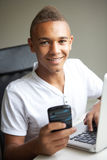 Teenage Boy Using Laptop And Mobile At Home Royalty Free Stock Images