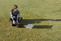 Teenage boy using laptop outdoors on grass Royalty Free Stock Photos