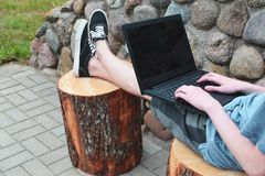 Teenage boy using laptop outside. Teenage boy wearing shorts and sneakers sitting on cut tree trunk and using black laptop with hands on keyboard on decorative Stock Image