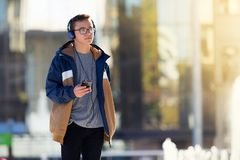 Teenage boy using smartphone and listening to music outdoors. Copy space stock images