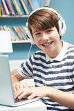 Teenage Boy Using Technology In Bedroom. Portrait Of Teenage Boy Using Technology In Bedroom Royalty Free Stock Photography