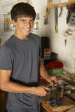 Teenage Boy Using Workbench In Garage Stock Photography