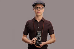 Teenage boy in a vintage outfit holding an old camera Royalty Free Stock Image