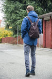 Teenage boy walking alone in street with backpack. Teenage boy walking alone in city street with backpack, seen from the back Royalty Free Stock Images