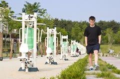 Teenage boy walks in park stock image