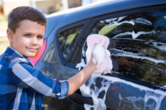 Teenage boy washing a car on a sunny day Royalty Free Stock Photo