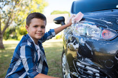 Teenage boy washing a car on a sunny day Royalty Free Stock Images