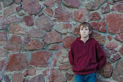 Teenage boy wearing burgundy hooded sweatshirt with vertical zipper leaning red granite boulders wall Stock Photos