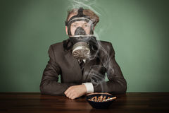 Teenage boy wearing a gas mask. And suit sitting in front on an ashtray filled with burning cigarette stubs and wafting smoke stock photos