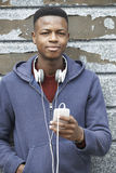 Teenage Boy Wearing Headphones And Listening To Music In Urban S Stock Photography