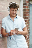 Teenage Boy Wearing Headphones And Listening To Music In Urban S. Teenage Boy Wearing Headphones And Listening To Music Royalty Free Stock Image